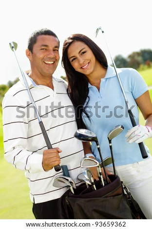 Happy couple playing golf at the club - stock photo