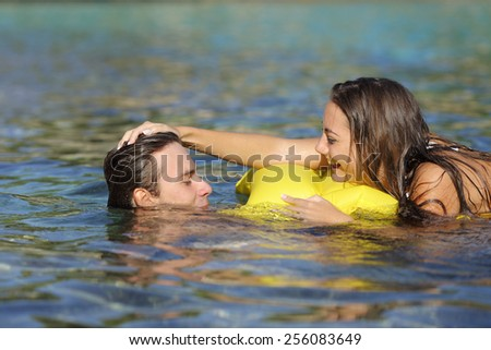 Happy couple playing on the beach in summer vacation while bathing - stock photo