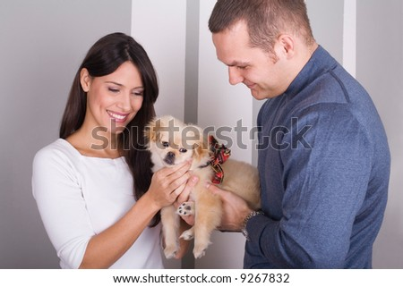 happy couple playing with the dog at home