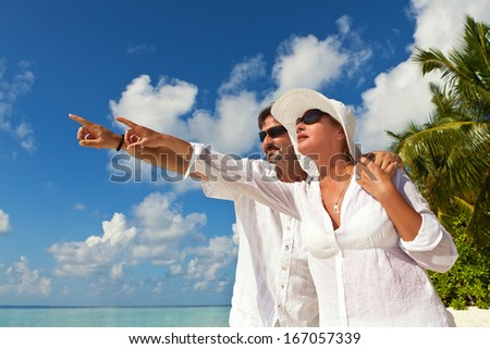Happy Couple pointing at something on the Beach  - stock photo