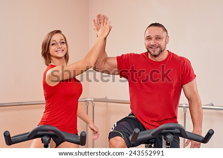 Happy couple portrait indoor biking in a fitness club - stock photo