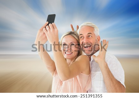 Happy couple posing for a selfie against serene beach landscape - stock photo