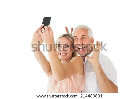 Happy couple posing for a selfie on white background - stock photo