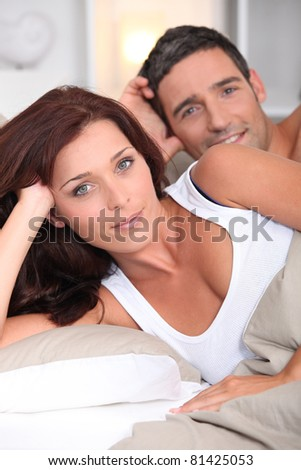 happy couple posing in bed - stock photo