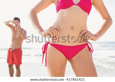 Happy couple posing on the beach on a sunny day