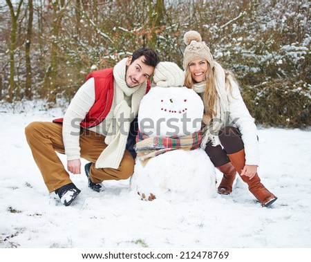 Happy couple posing with a snowman outside in winter