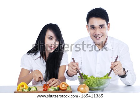 Happy couple preparing salad together. isolated on white background