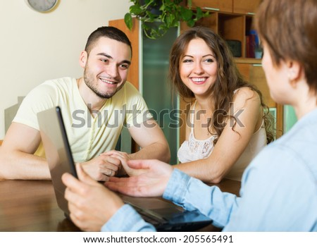 Happy couple questionnaire for social worker or employee of the company at table
