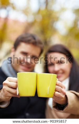 Happy couple raising glasses with hot tea in autumn - stock photo