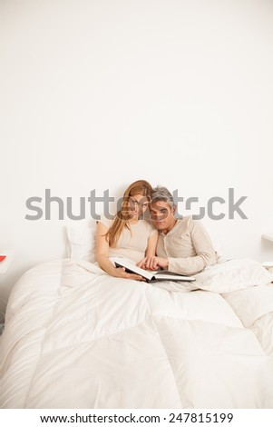Happy couple reading a book inside the bed - stock photo