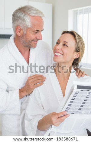 Happy couple reading newspaper together in bathrobes at home in the kitchen