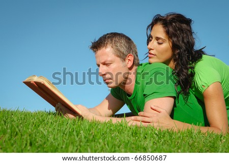 happy couple reading outdoors in summer - stock photo