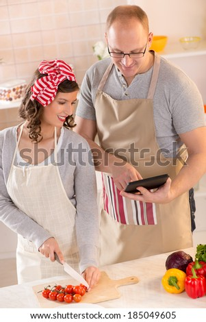 Happy couple reading recipe for tablet and preparing food in the kitchen