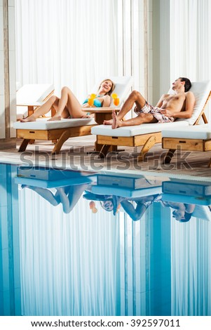 Happy couple relaxing at swimming pool - stock photo