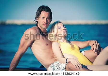 Happy couple relaxing at the beach. - stock photo