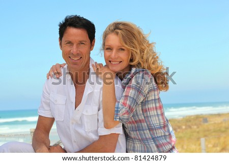 Happy couple relaxing at the beach - stock photo