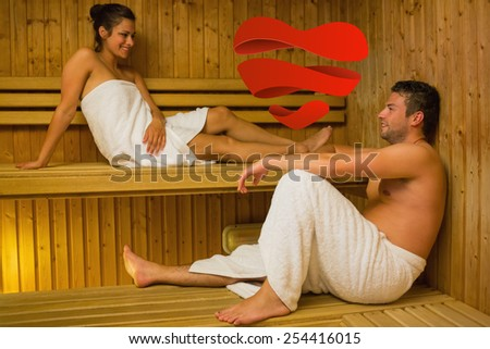 Happy couple relaxing in a sauna and chatting against heart - stock photo