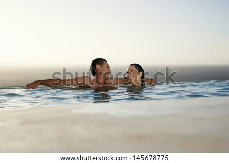 Happy couple relaxing in infinity pool at resort - stock photo