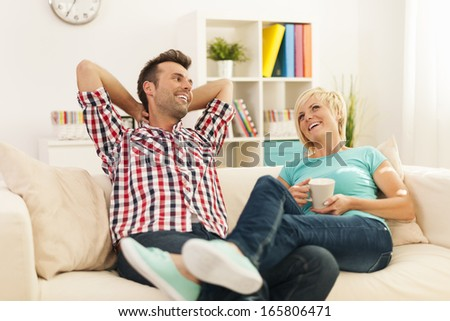 Happy couple relaxing in living room  - stock photo