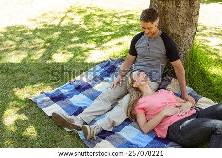 Happy couple relaxing in the park on a sunny day - stock photo