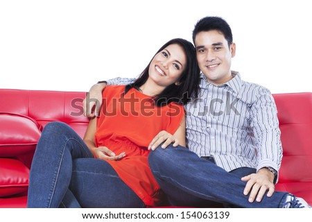 Happy couple relaxing on a red sofa over white background - stock photo