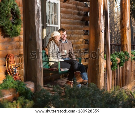 Happy Couple Relaxing on Log Cabin Porch - stock photo