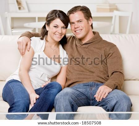 Happy couple relaxing on sofa in livingroom - stock photo