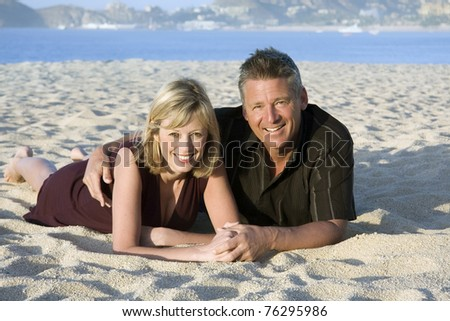 Happy couple relaxing on the beach. - stock photo