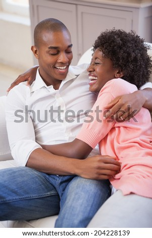 Happy couple relaxing on the couch at home in the living room - stock photo