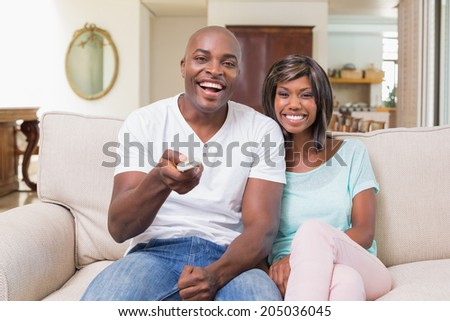 Happy couple relaxing on the couch watching tv at home in the living room - stock photo