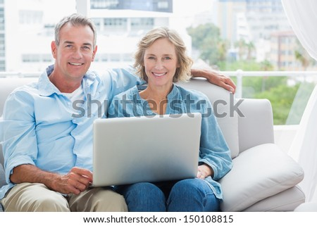Happy couple relaxing on their couch using the laptop smiling at camera at home in the sitting room