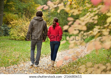 Happy couple resting and walking in autumn forest  - stock photo