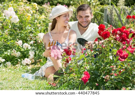 Happy couple resting at the flowers garden and smiling at summer resident