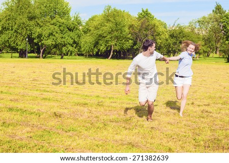 Happy Couple Resting Outdoors and Having Very Good Time Running Together with Hands Connected.Horizontal Image - stock photo