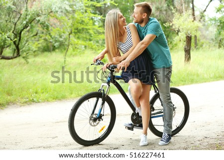 Happy couple riding bicycle in the park