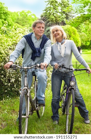 Happy couple riding bicycles outside - stock photo