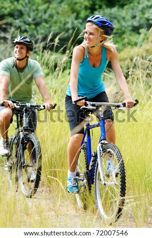 Happy couple riding bicycles outside, healthy lifestyle fun concept - stock photo