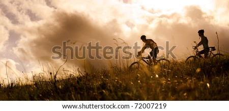 Happy couple riding bicycles outside, healthy lifestyle fun concept. silhouette at sunset panoramic - stock photo