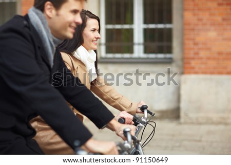 Happy couple riding bikes together in a city - stock photo