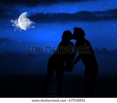 Happy couple romantically kissing at night under moonlight - stock photo