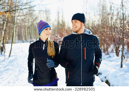 Happy couple running at park during winter