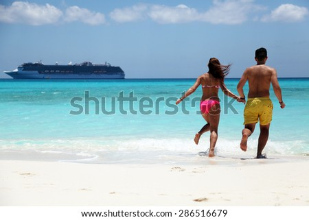 happy couple running in water at the beach with cruise ship close to shore on sunny day