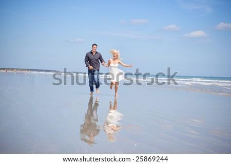 Happy couple running on a beach. - stock photo