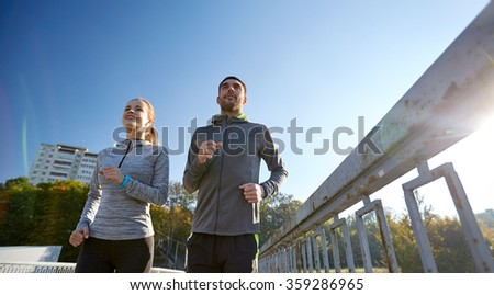 happy couple running outdoors - stock photo