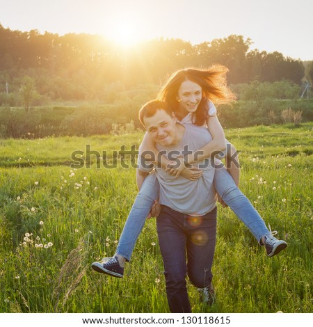 happy couple running outdoors at sunset - stock photo