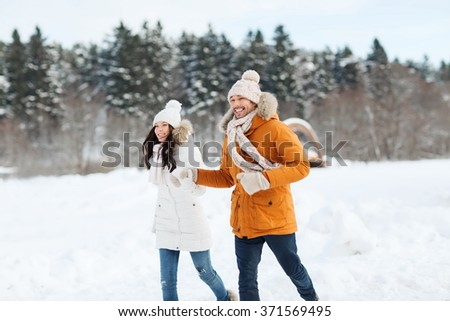 happy couple running over winter background