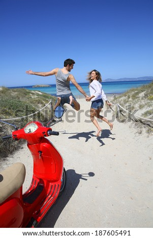 Happy couple running to the beach, scooter in foreground - stock photo
