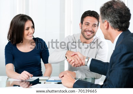 Happy couple seal a deal with their personal financial advisor at home - stock photo