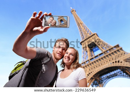 happy couple selfie by smart phone in Paris with eiffel tower, caucasian - stock photo