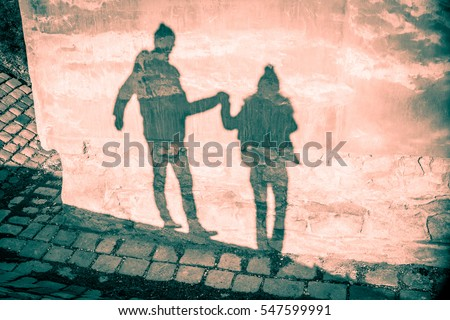 Happy couple shadow silhouettes in winter clothing holding their hands and walking against grunge old mauve pink wall and stone pavement background - Saint Valentine Day card backdrop